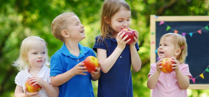 children outside eating apples